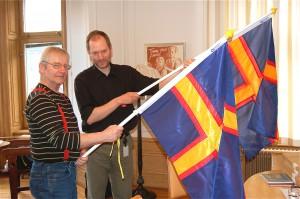 Ledamöterna Björn Ståbi och Lars Ilshammar visar upp Hälsinge Akademins flagga, som formats av framlidne konstnären Bisse Thofelt, en av föreningens stiftare. Flaggan har inte blivit någon officiell hälsingeflagga.